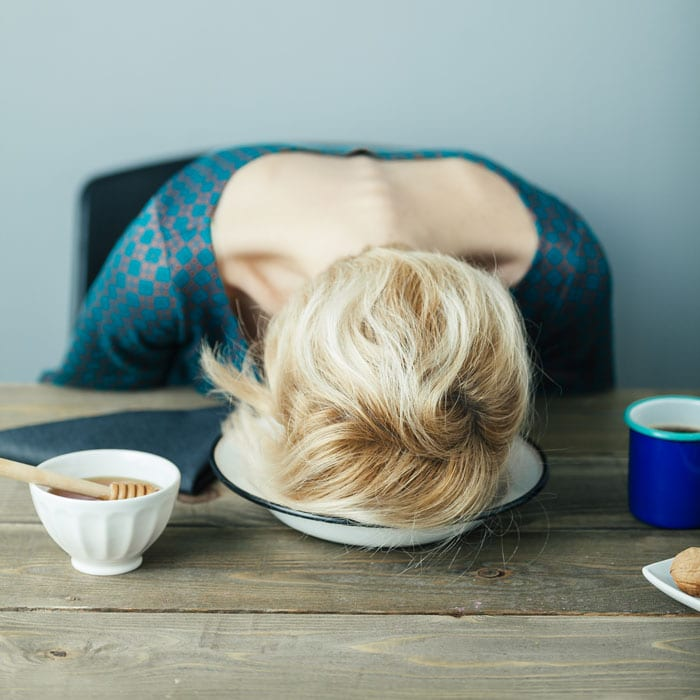 woman tired with her head down on table sleeping