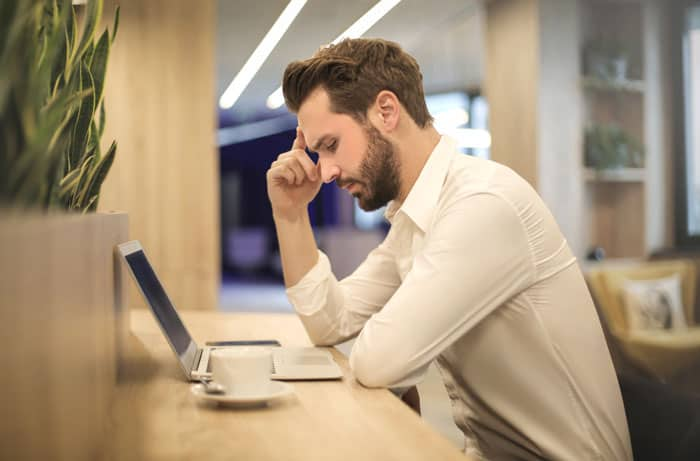 man with headache sitting at computer