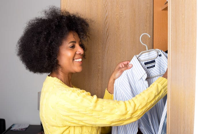 woman tidying clothes in closet