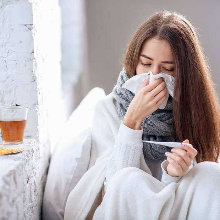 woman with the flu taking temperature
