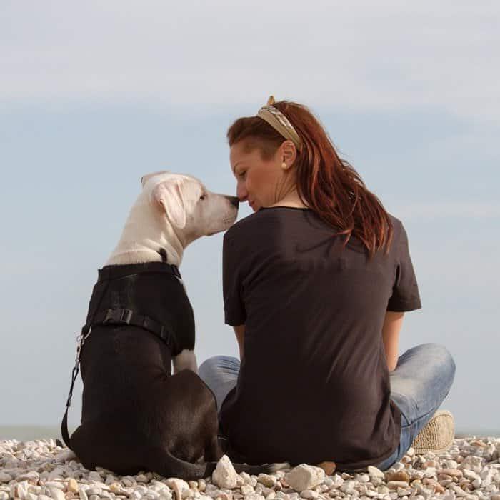 woman kissing dog beach