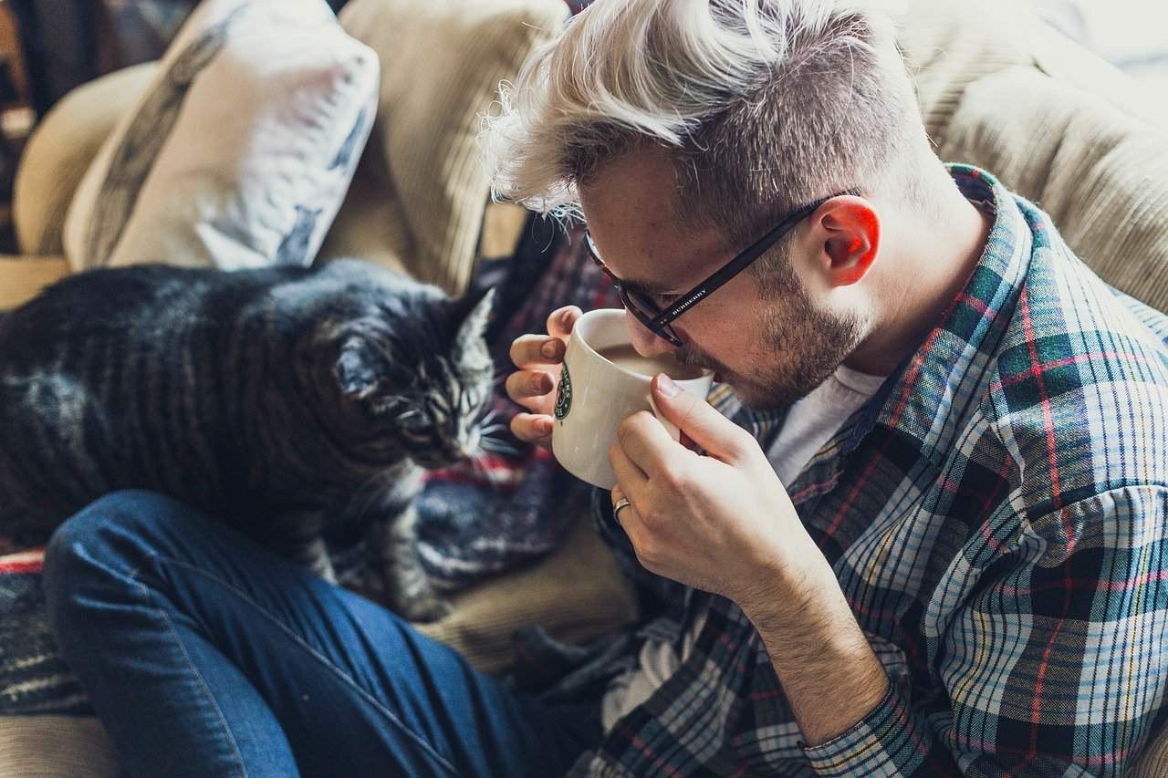 adult man relaxing with coffee and cat self care