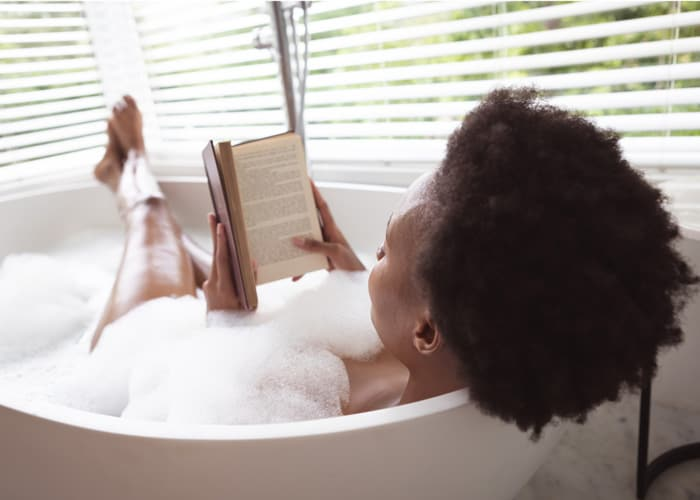 woman relaxing in bath with book