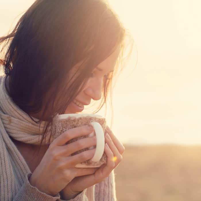 woman holding mug in sunrise